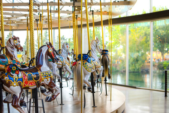 Carousel horses sitting empty at an indoor merry go round carousel in Spokane, Washington with the park and Spokane River blurred in the distance