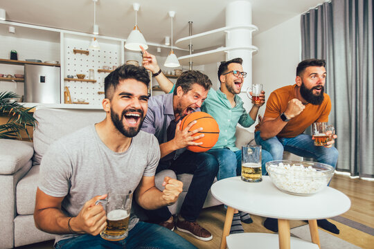 Happy friends or basketball fans watching basketball game on tv and celebrating victory at home.