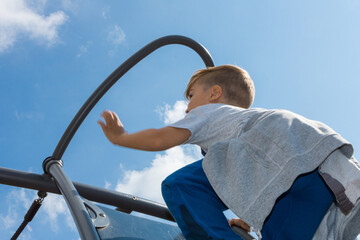 Low Angle View Of Boy Climbing On Monkey Bars Against Sky