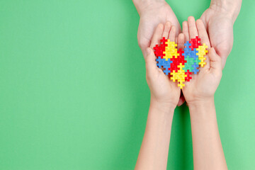 Fototapeta Adult And Kid Hands Holding Colorful Heart On Green Background. World Autism Awareness Day Concept. obraz