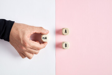Fototapeta Male hand holding a wooden cube with the word plan pointing at the options of A or B. Business plan decision or choice obraz