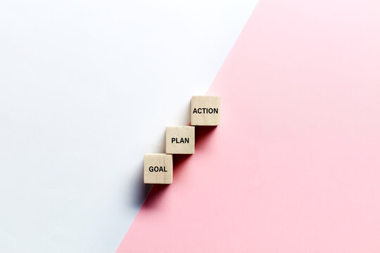 The words goal, plan and action on wooden cubes against pink and white background. Business or marketing planning strategy