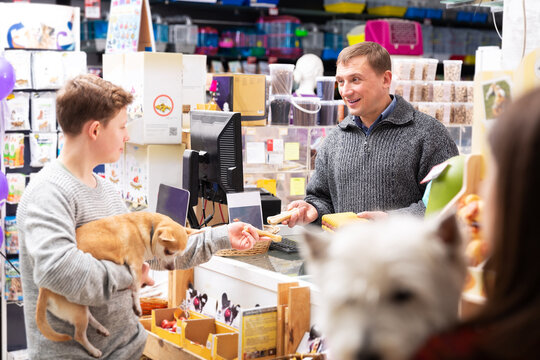 Cheerful positive man seller offering goods to customer teenager in pet shop