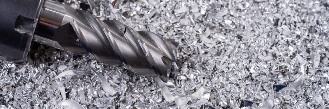 Panoramic image. Silver end mill cutter with metal shavings. Processing of ferrous metals in a factory