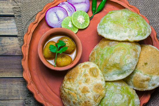 Traditional Bengali cuisine - Green peas kachori or Koraishutir kochuri in a earthenware plate along with a bowl of Spicy dum aloo curry, onion, lemon and green salad.