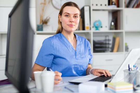 Young woman doctor assistant working in medical office using laptop computer