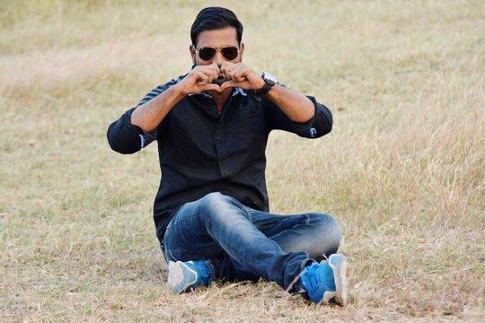Man Wearing Sunglasses Making Heart Shape While Sitting On Land