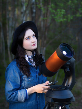 Portrait of young woman looking through the telescope on the hil