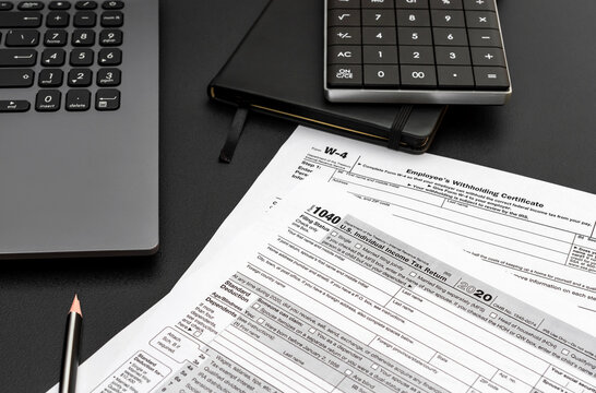 Tax forms with laptop, notepad and calculator on black office desk. Filing tax form.