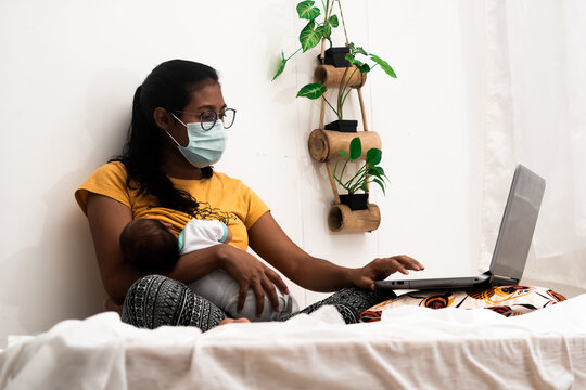 Young Hispanic mother in a face mask working from home while breastfeeding her baby