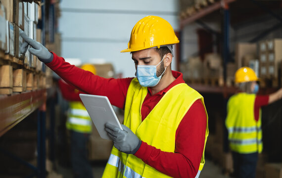 Young man working in warehouse doing inventory using digital tablet and loading delivery boxes plan while wearing face mask during corona virus pandemic - Logistic and industry concept
