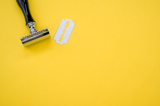 Top view of a mechanical razor and blade isolated on yellow background