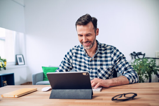 Smiling man working at a desk from home using digital tablet