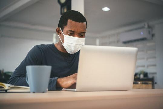African American Man in quarantine wearing protective face mask using laptop during coronavirus pandemic.