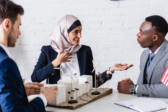 smiling arabian businesswoman pointing with hand while talking to african american business partner near model of green power station, blurred foreground