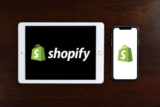 Shopify logo displayed in full screen on iPad and iPhone placed on wooden table. Shopify is an e-commerce platform for online stores and retail point-of-sale systems.
