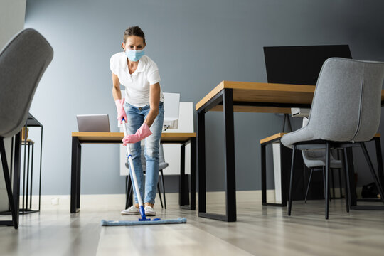 Female Janitor Mopping Floor In Face Mask