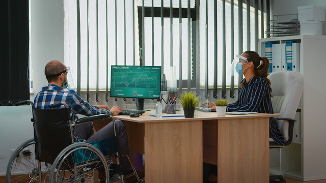 Manager with disability comming with wheelchair at workplace with protection mask working in new normal business office. Immobilized freelancer in financial company respecting social distance.