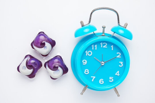 A picture of 3 in 1 laundry detergent pod and alarm clock on isolated white background. Economic and environment friendly for clothes washing