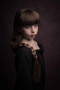 Classic painterly dark renaissance portrait of a girl in black dress with a long braid hanging across her shoulder