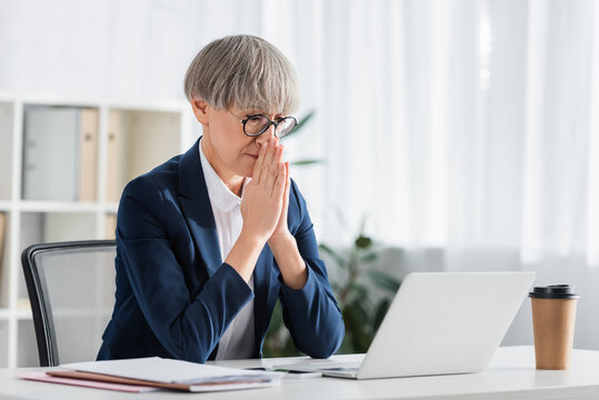 worried team leader in glasses with praying hands looking at laptop on desk