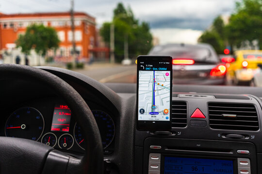 Driving and using waze maps application on smartphone on car dashboard, Driver using maps app for showing the right route through the traffic of city. Bucharest, Romania, 2020.