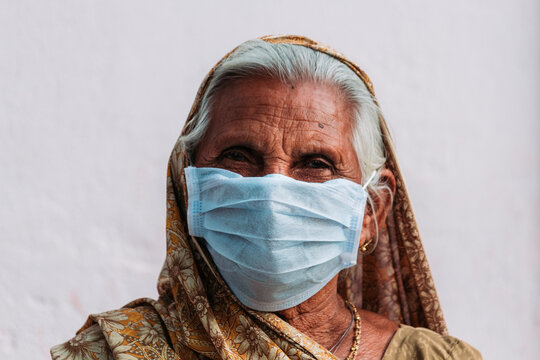 Close-up Portrait Of Senior Woman Wearing Mask Against White Wall