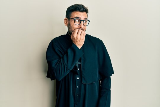 Young hispanic man wearing priest uniform standing over white background looking stressed and nervous with hands on mouth biting nails. anxiety problem.