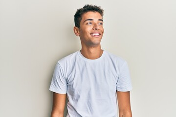 Young handsome african american man wearing casual white tshirt looking to side, relax profile pose...