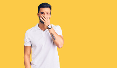 Fototapeta Young handsome hispanic man wearing casual clothes smelling something stinky and disgusting, intolerable smell, holding breath with fingers on nose. bad smell