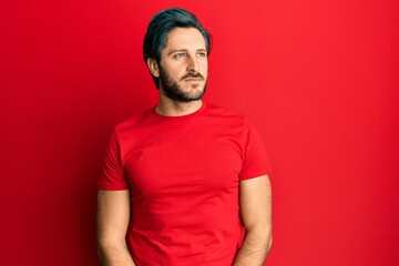 Young hispanic man wearing casual red t shirt smiling looking to the side and staring away thinking.