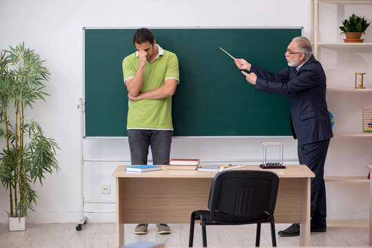 Aged teacher and male lazy student in the classroom