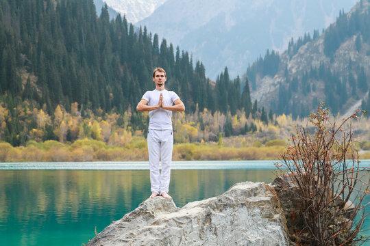 Young zen man in meditation. Outdoor yoga in mountain lake