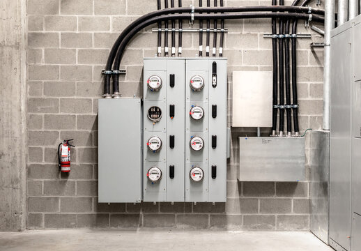Electrical room with multiple smart meters, cabinets, wiring and fire extinguisher. Below-grade service room of 4 story strata building with residential or commercial units. Selective focus.