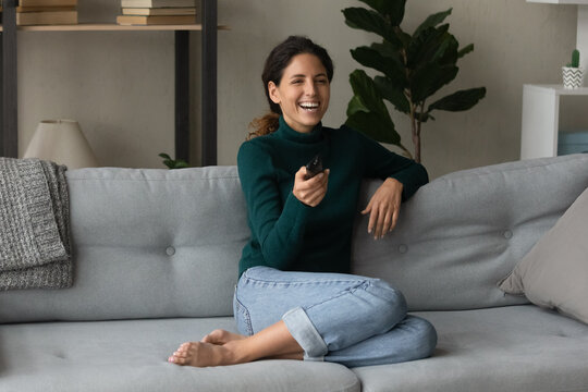 Overjoyed millennial Caucasian woman sit relax on sofa in living room enjoy cozy domestic weekend. Happy young 20s female rest on couch at home laugh watching TV program. Entertainment concept.