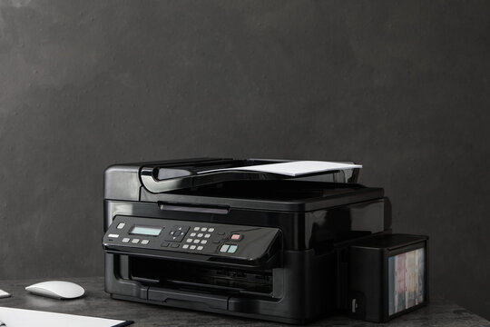 Modern printer with paper on grey table at workplace