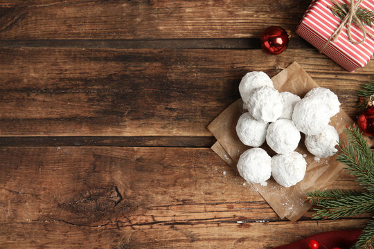 Tasty snowball cookies and Christmas decorations on wooden table, flat lay. Space for text