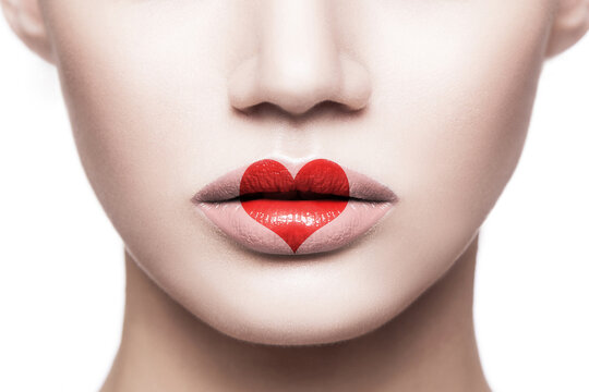 Closeup portrait of beautiful woman face with makeup and red heart shape on her lips. valentines day and beauty love and care concept. indoor studio shot, Isolated on white background.