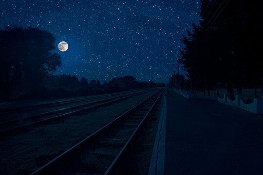 Empty and abandoned train station at night. Full moon over railroad.