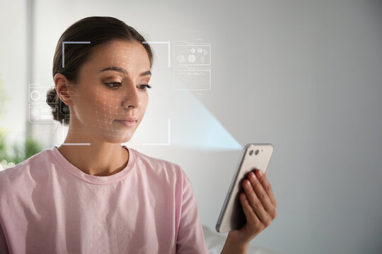 Young woman unlocking smartphone with facial scanner indoors. Biometric verification