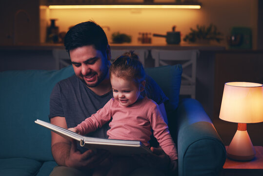 happy father is reading a fairytale book to toddler baby girl at home. bedtime story
