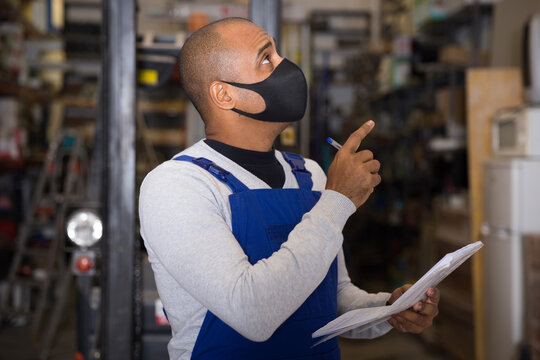 Warehouse manager in protective mask calculates the quantity of goods and writes it down in a notebook