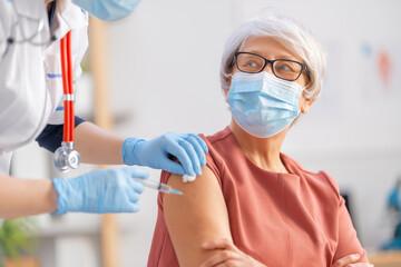 Doctor giving a senior woman vaccination