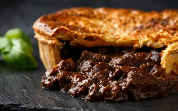 British beef steak pie with onion, wine gravy on rustic stone board