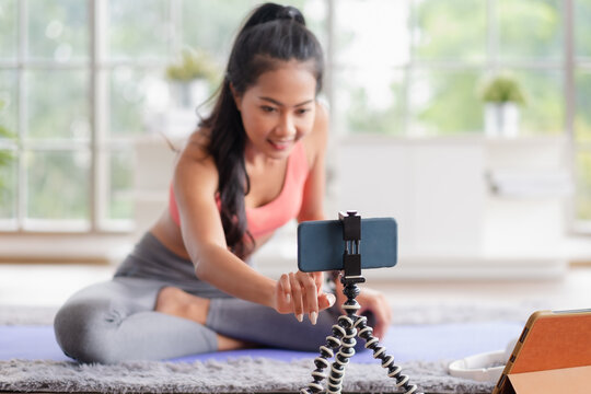 asian trainer woman live streaming on social media about wellness exercise at home.Influrencer marketing trainning course online.new normal fitness class