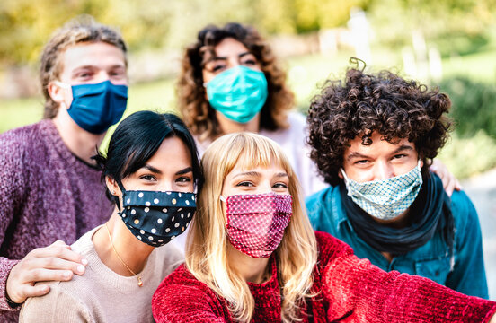 Multiracial people taking selfie wearing face mask and spring clothes - New normal lifestyle concept with young friends having fun together outside - Bright filter with focus on central blond girl