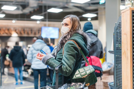 Woman standing in queue at cash desk in supermarket wearing mask