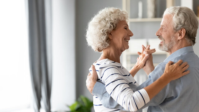 Happy romantic middle aged older retired family couple dancing slowly to favorite music, enjoying home dating or celebrating wedding anniversary together, showing love devotion and care, copy space.