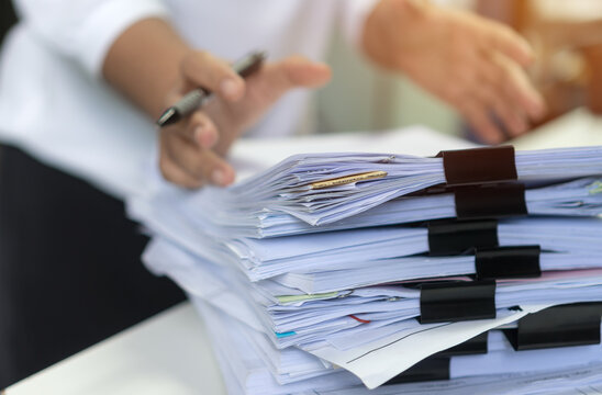 Employee woman hands checking Business unfinished Documents  with stacks paper files and searching document achieves preparing meeting planing at busy work desk office