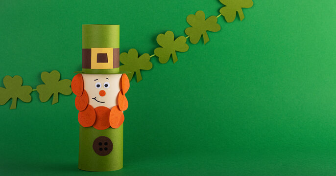 Green cute Leprechaun made of handmade paper with four-leaf clover on a green background, space for text